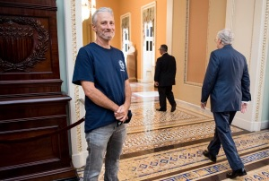 Jon Stewart laughs as Mitch McConnell walks by